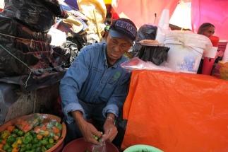 ein Herr am Gemüse abpacken zerquetscht zwischen anderen Marktständen
